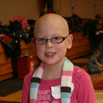 Young girl with bald head smiling and hopeful
